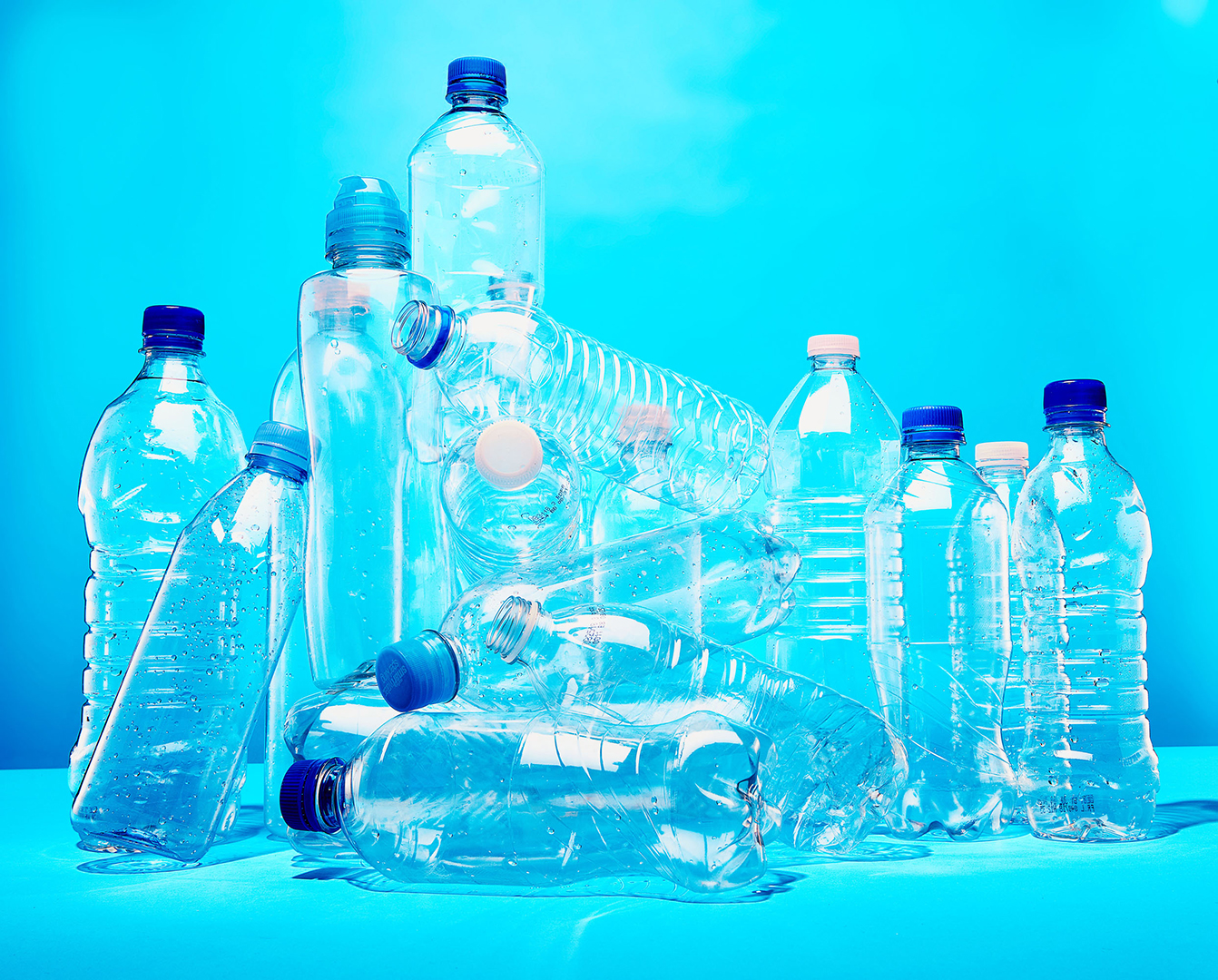 plastic bottles in a pile against blue background