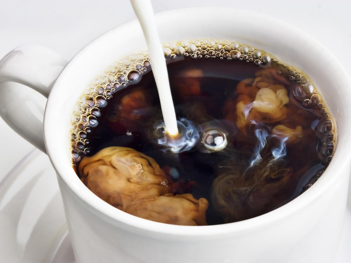 Milk Pouring In Cup of Coffee