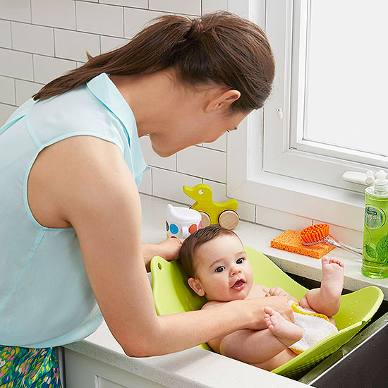 Mother washing baby in sink with green tub