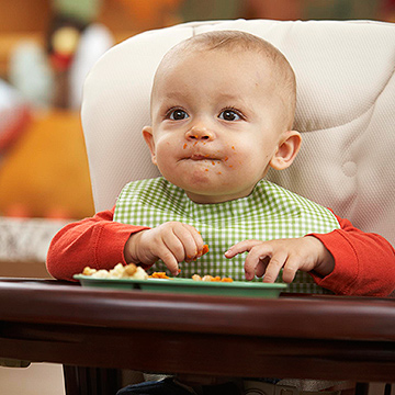 Baby in high chair with checkered bib