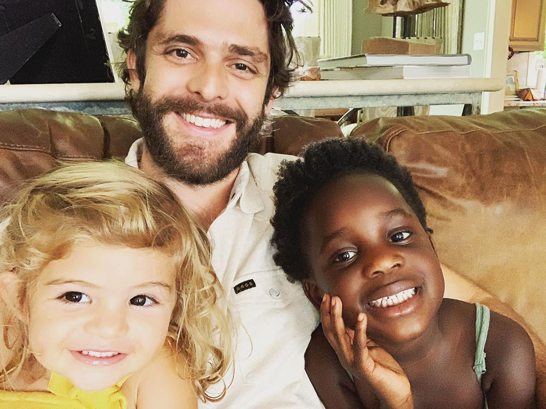 Thomas Rhett with Children on Sofa Smiling
