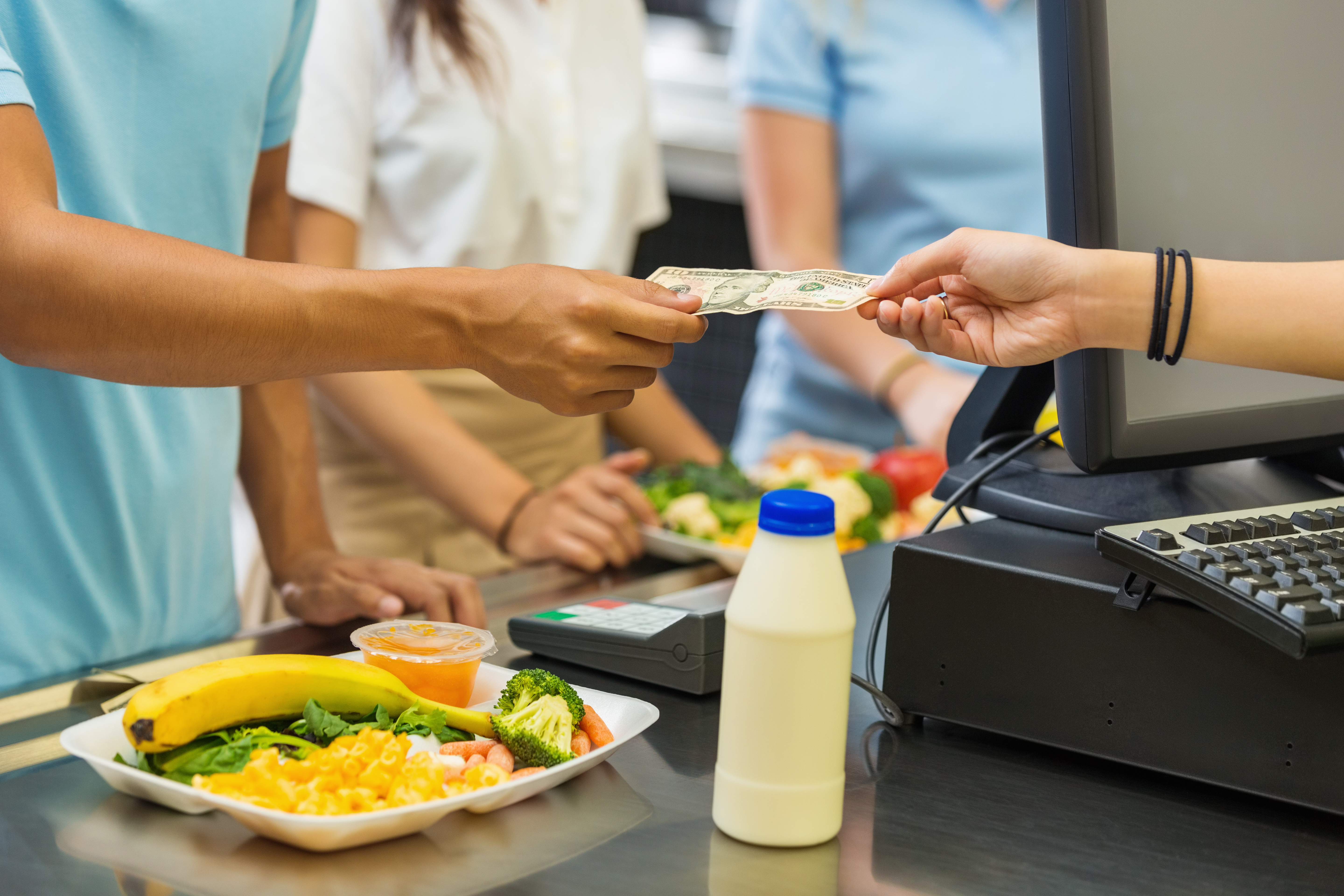Student paying for school lunch with cash in cafeteria