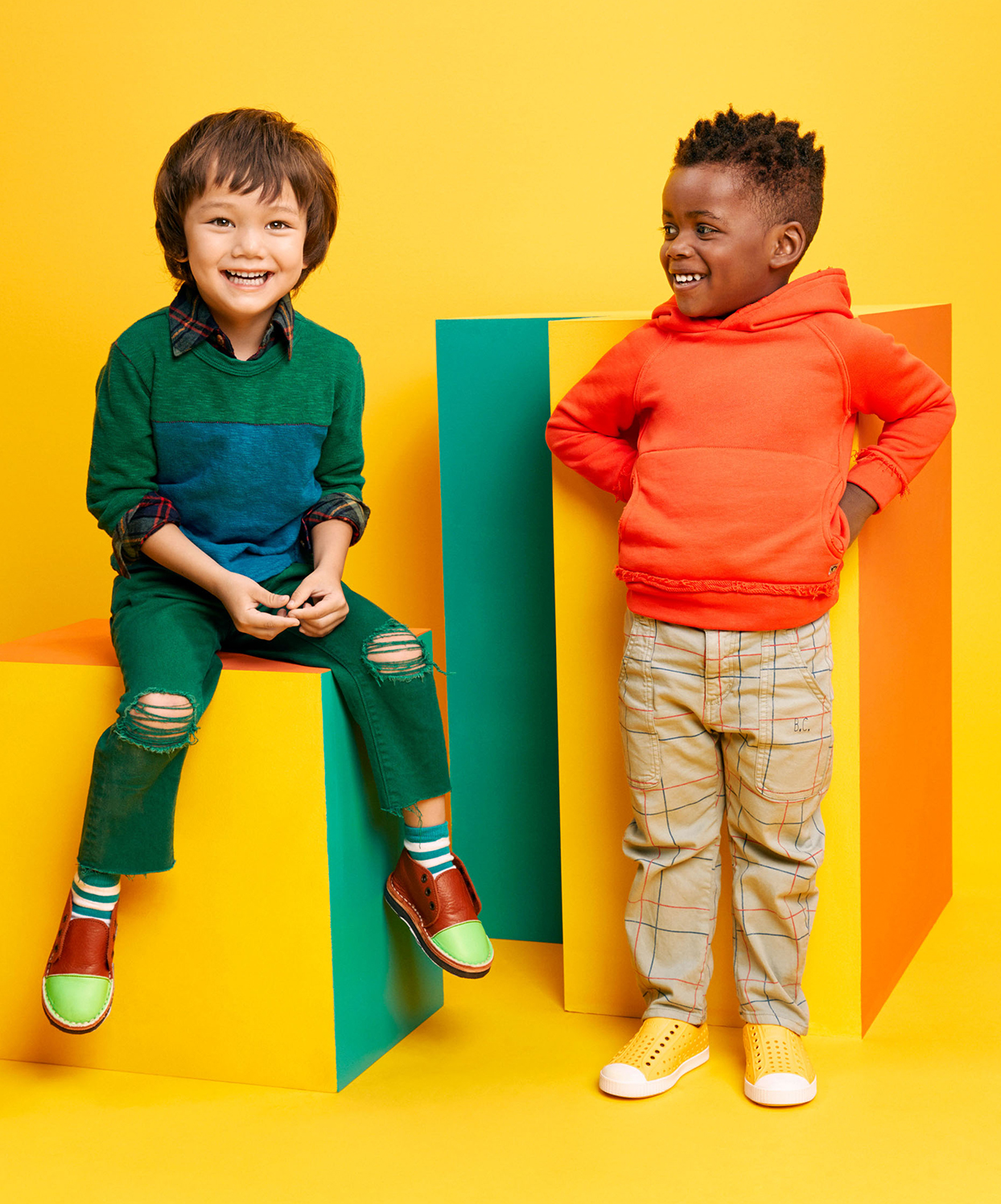 two boys yellow background smiling on blocks