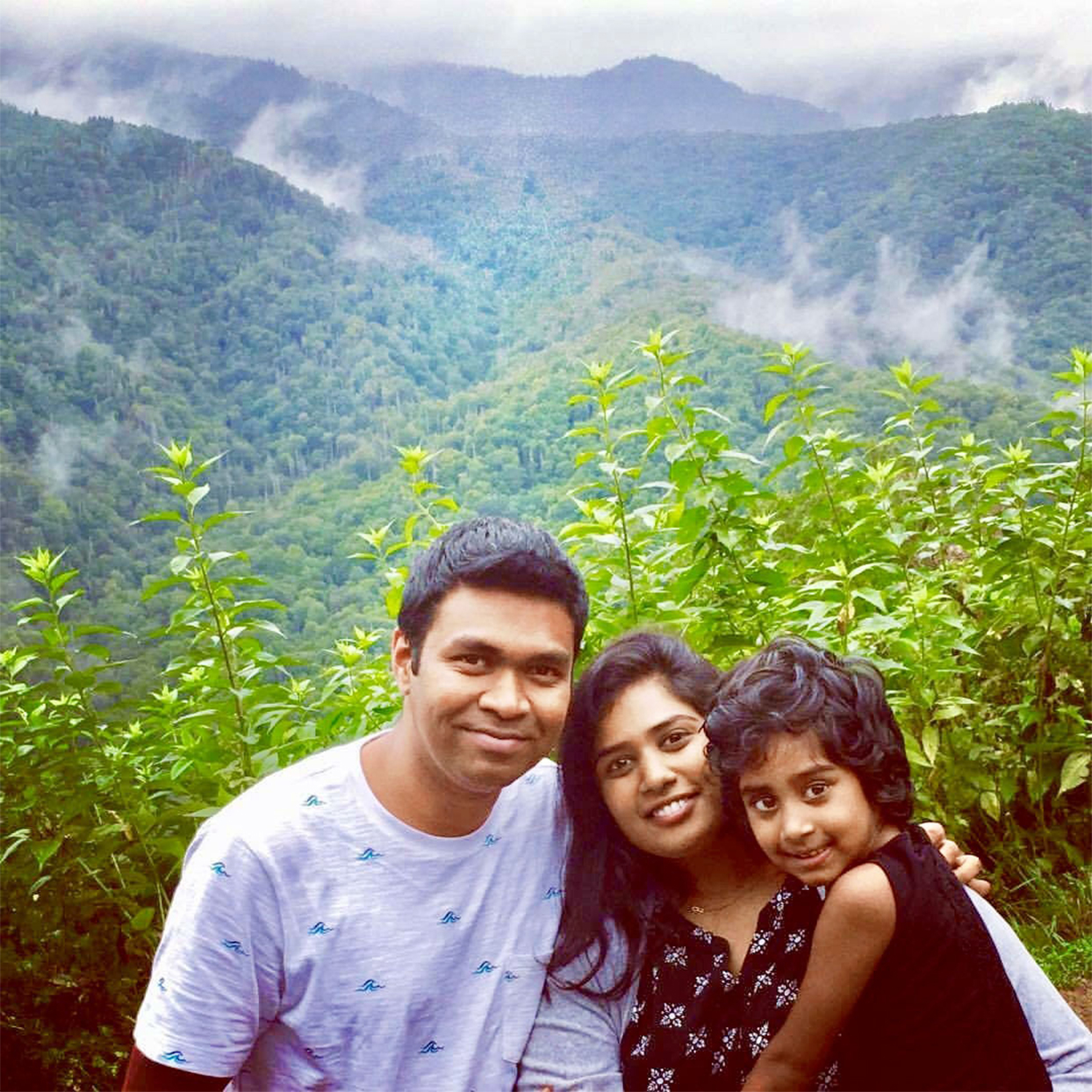 husband wife and daughter in front of natural indian landscape