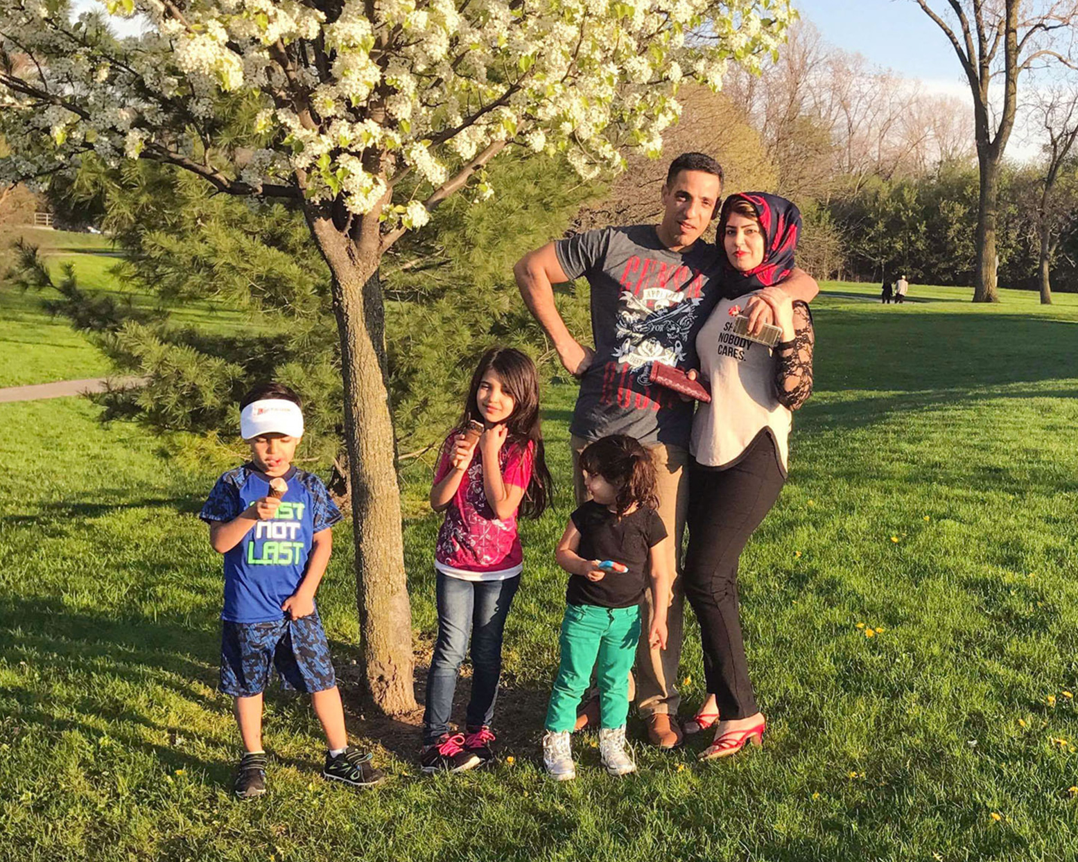 husband wife two daughter and one son eating ice cream beneath tree