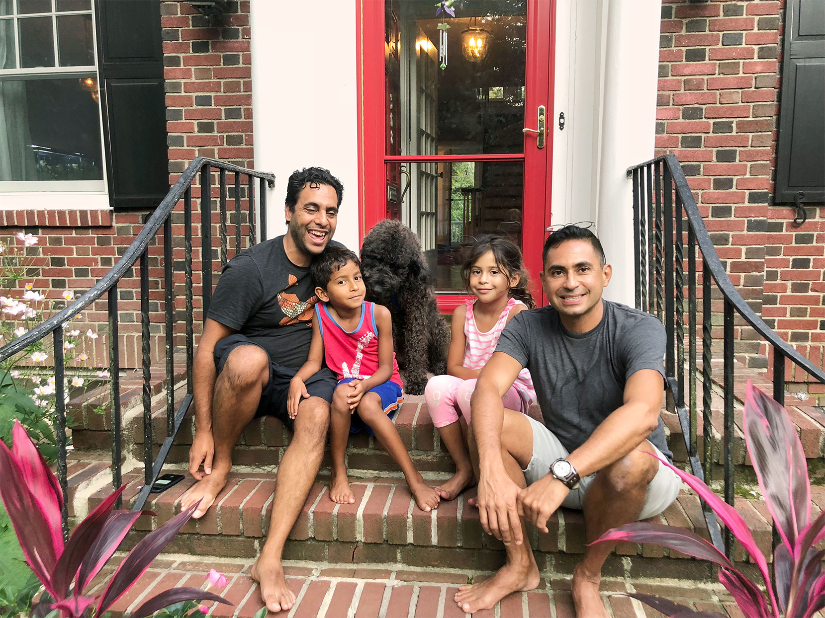 husbands sitting with boy and girl twins and dog on front porch