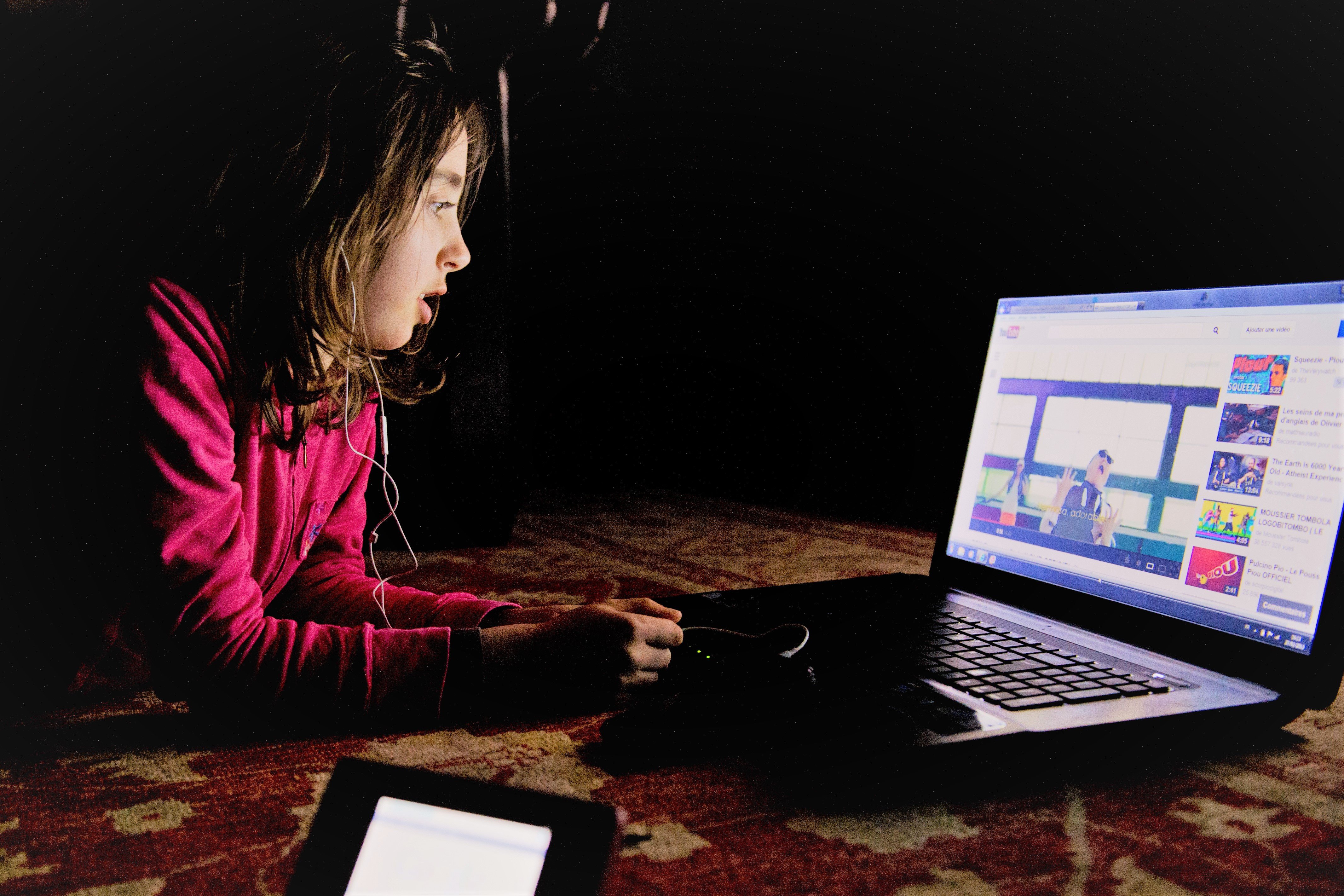 Girl Watching a Video on Youtube on Computer Laying on Carpet Floor
