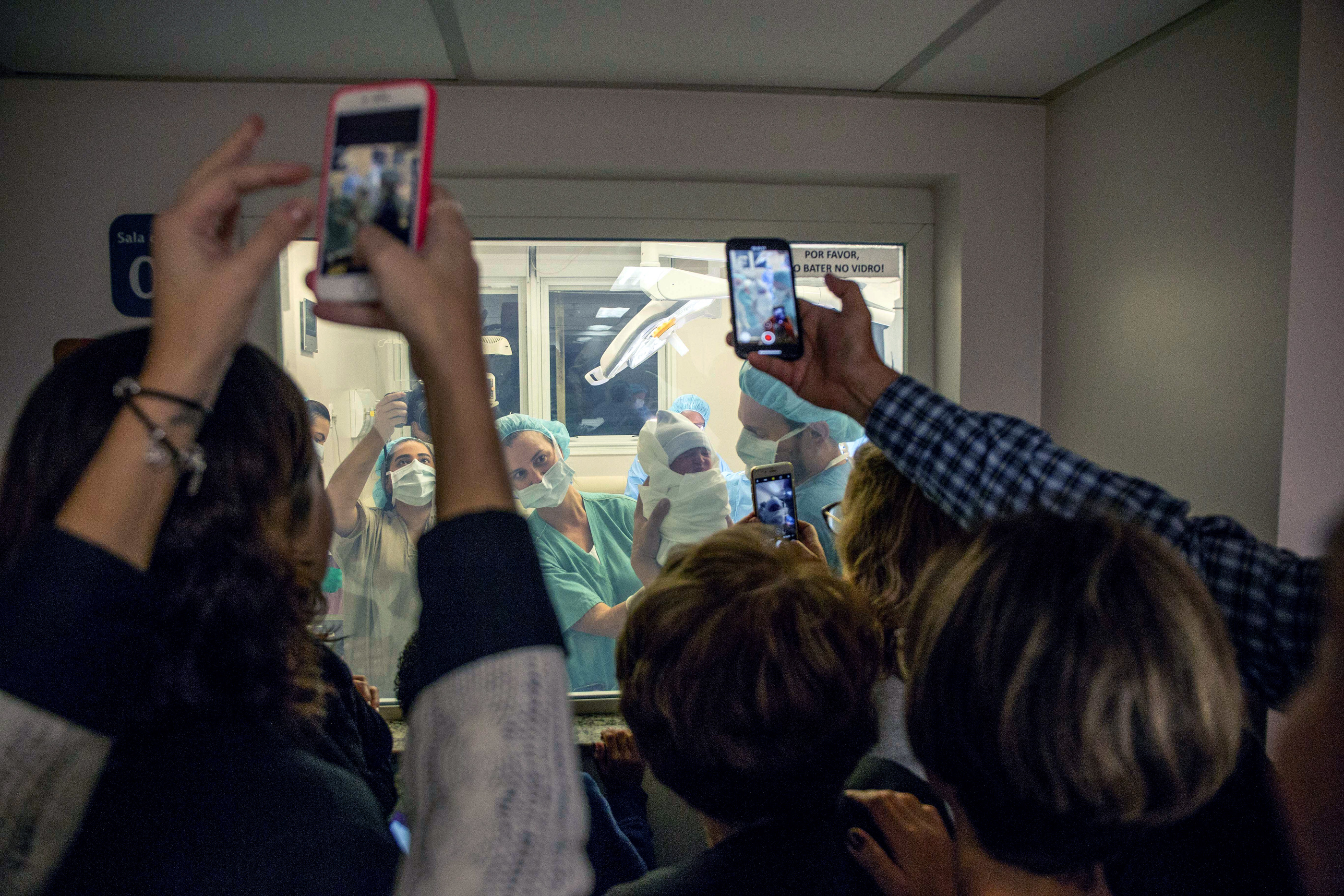 Relatives photograph the moment when Mariana Casmalla gave birth to Lorena via C-section, in the Maternity Hospital Albert Einstein on May 24 in São Paulo.