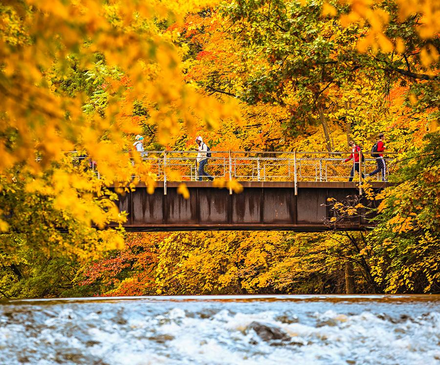 Students cross the Red Cedar River.