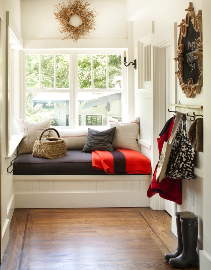 A white mudroom with a cozy window bench.