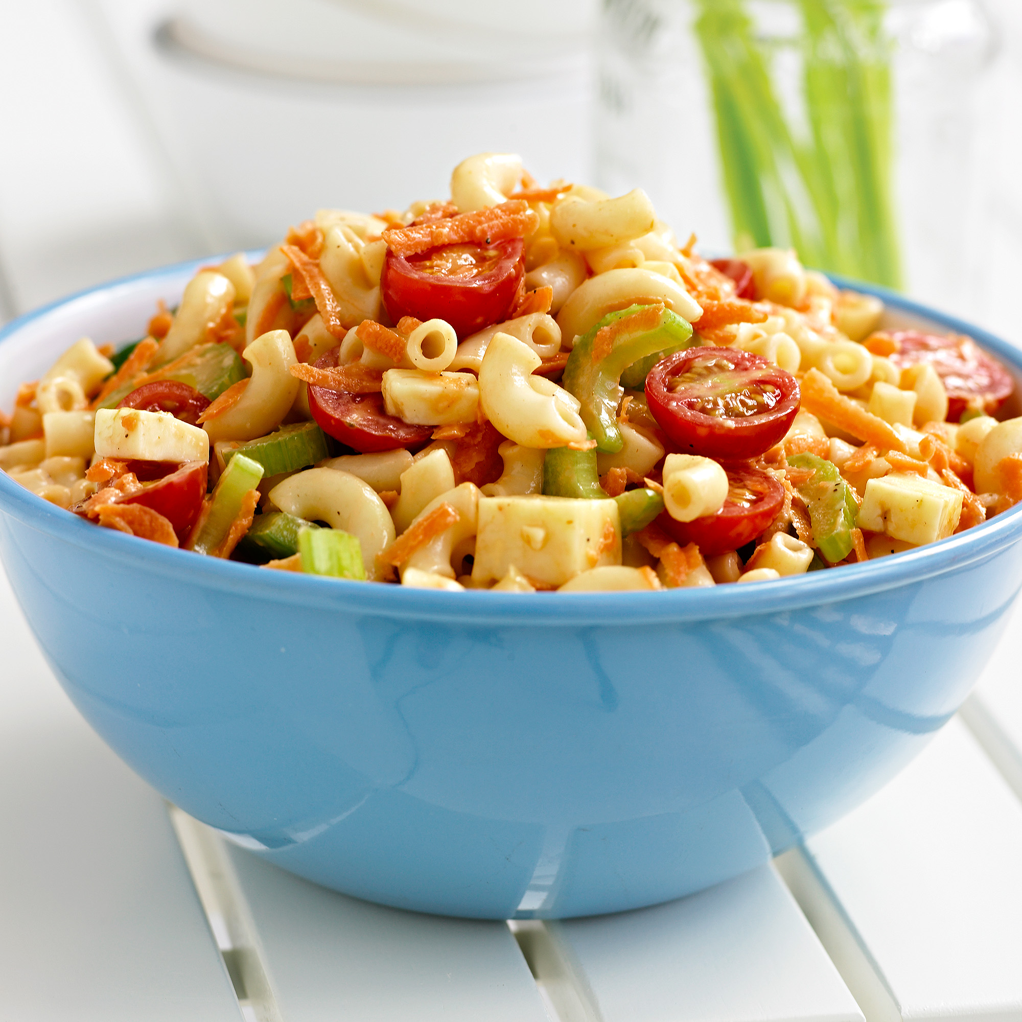 macaroni salad with cherry tomatoes in blue bowl
