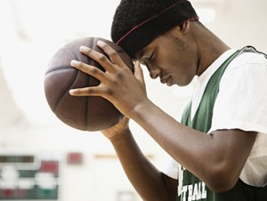 african-american-basketball-player-leaning-head-on-ball-2.jpg