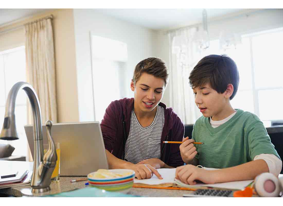 Teen boy assisting brother in doing homework