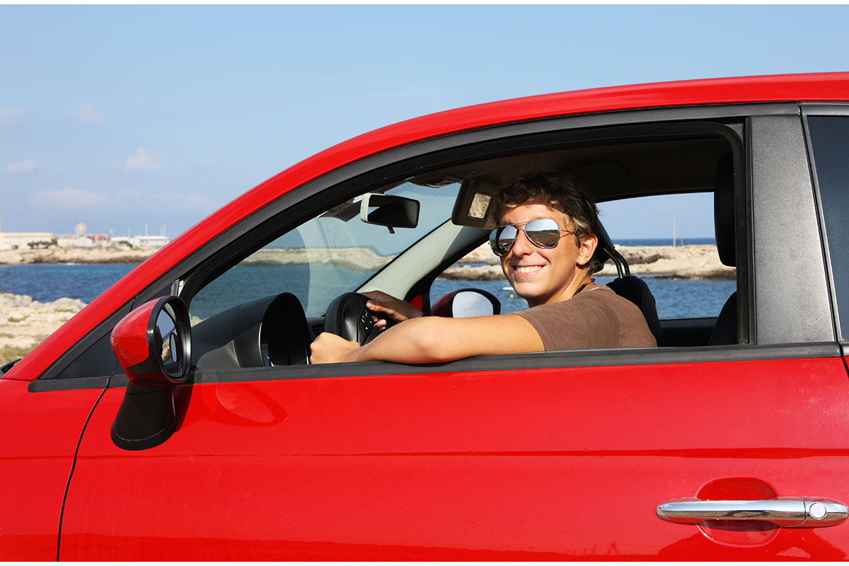 teen boy driving red car wearing sunglasses