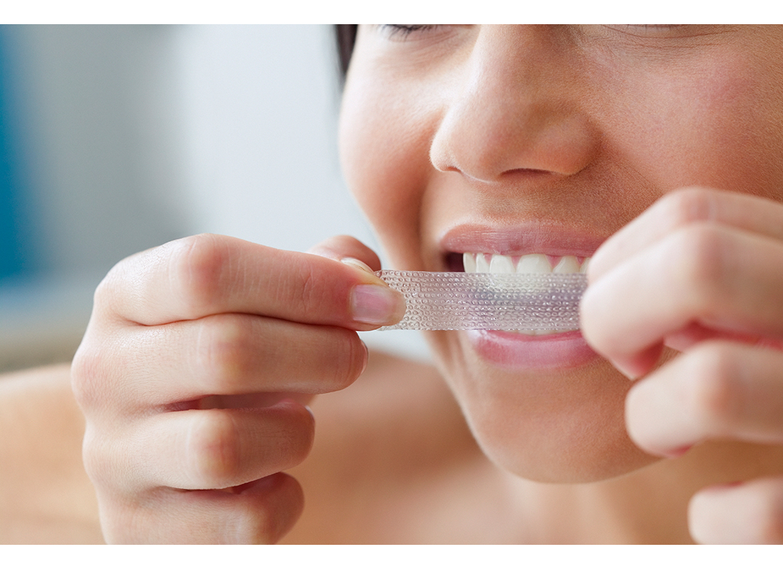 woman applying white strips to teeth