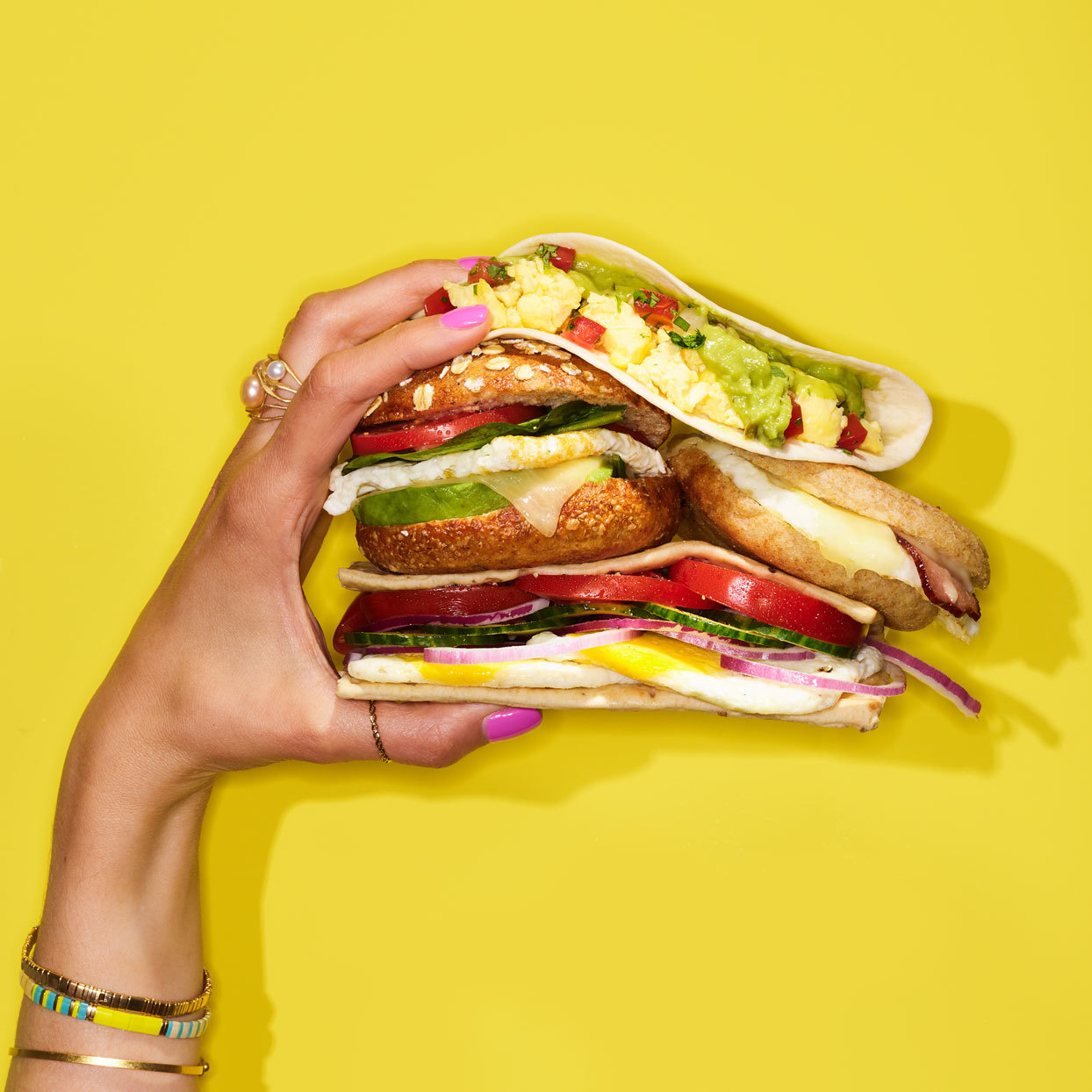 hand holding several precariously stacked breakfast sandwiches