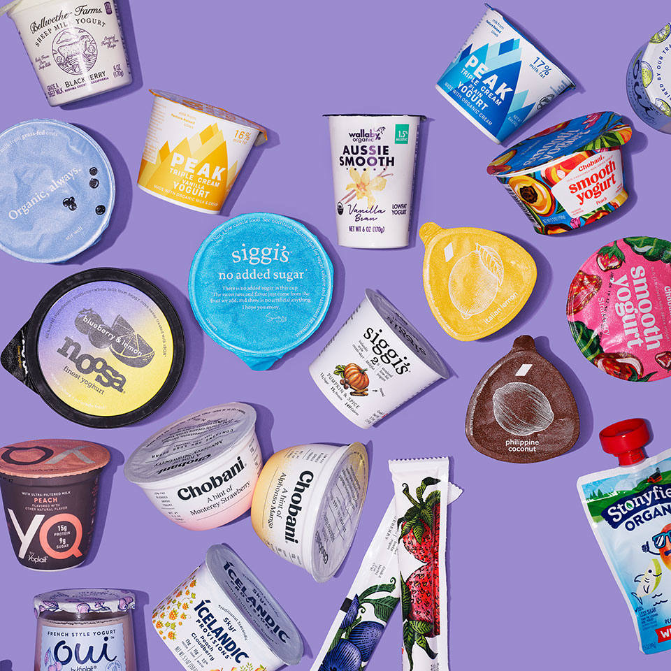 many different brands of packaged yogurt from overhead with purple background