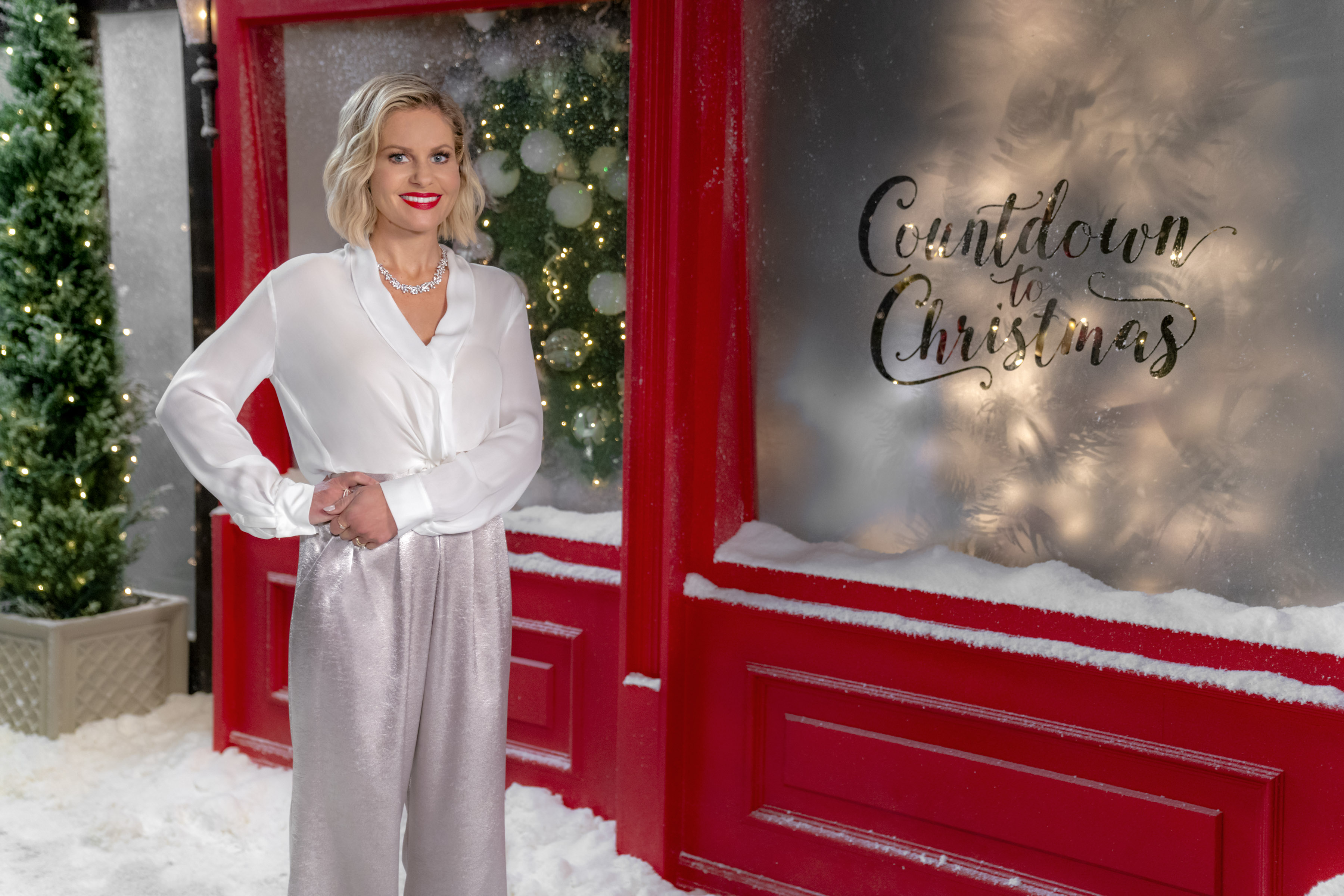 candace cameron bure dressed in a white top and silver pants standing outside in the snow next to a red wall and window that says countdown to christmas
