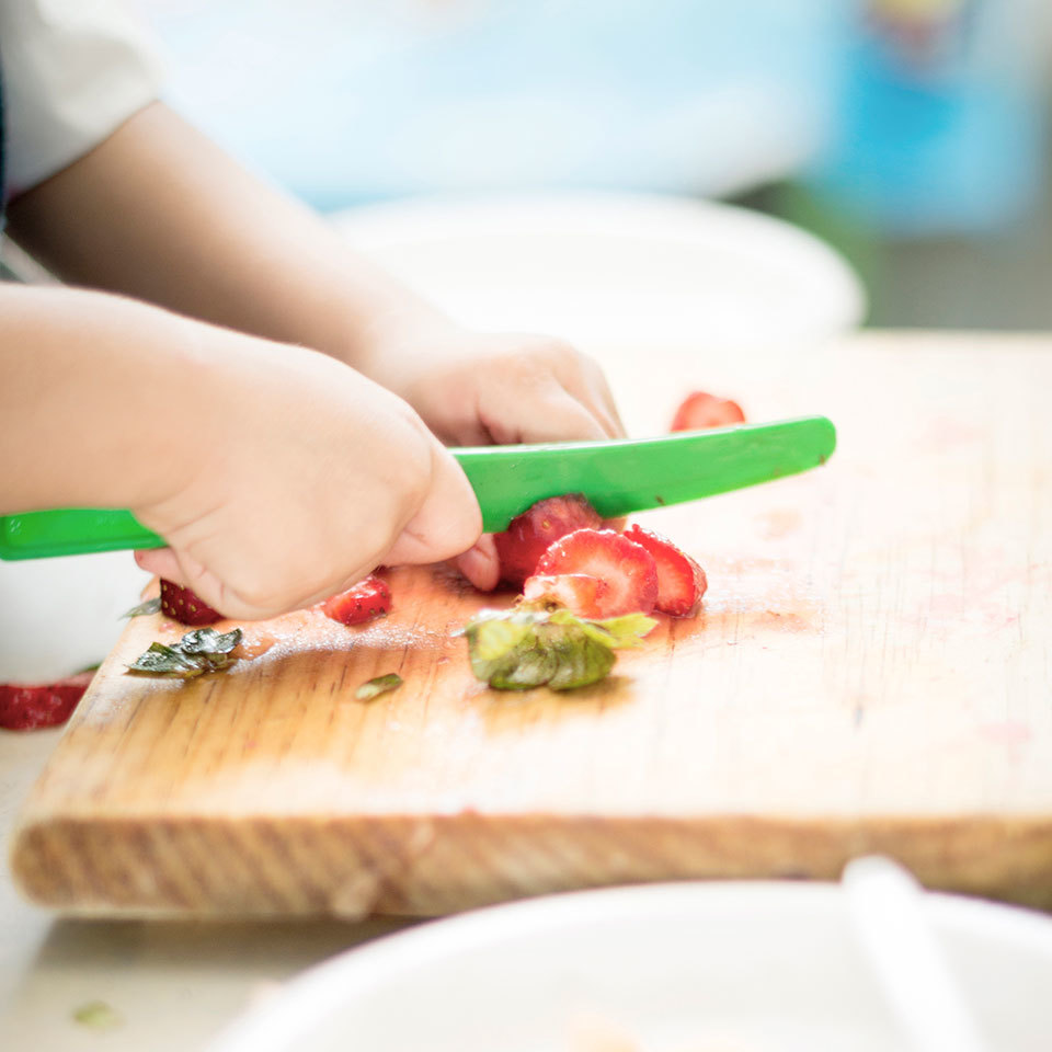 Child cutting strawberries with plastic knife