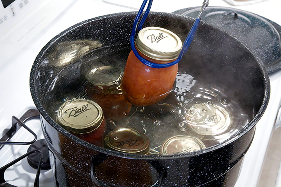 adding jam jars to a pot of simmering water
