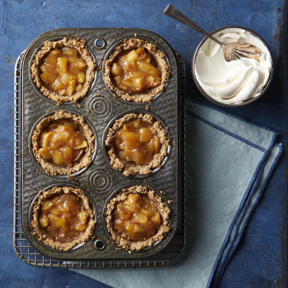 no-sugar-added mini apple pies in muffin tin on table with side of whip cream