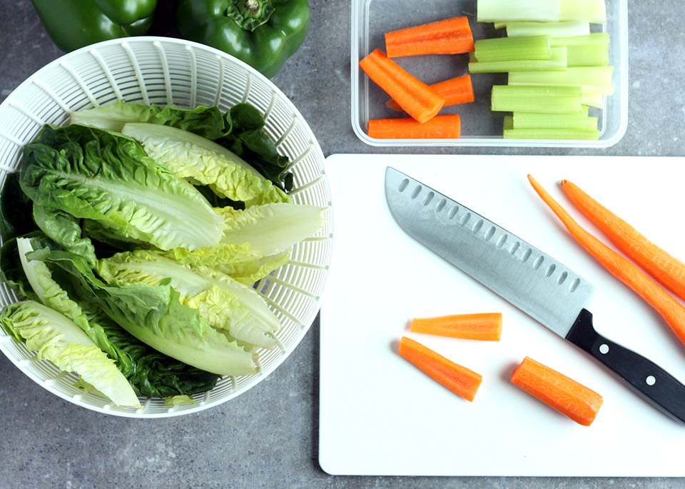 lettuce in salad spinner and carrots on cutting board with knife