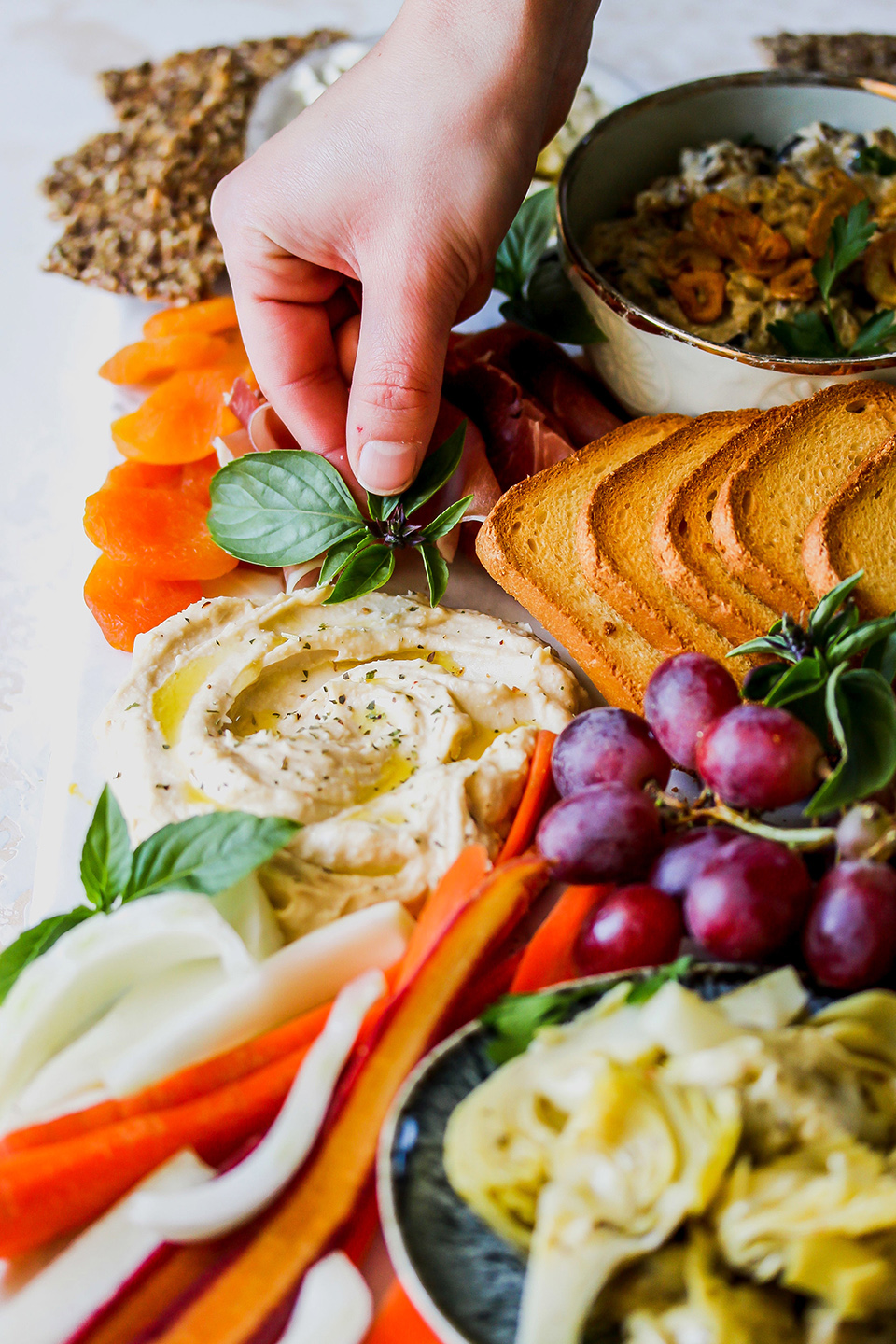 mediterranean appetizer spread with hummus, grapes, crackers, carrots, and apricots