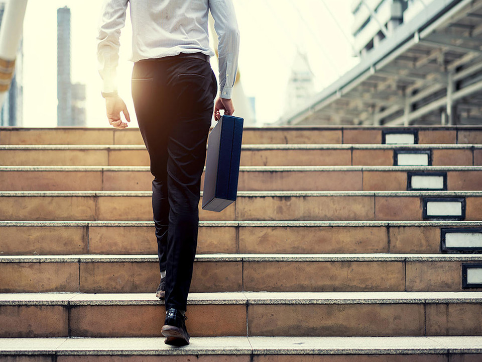 man walking up steps with briefcase