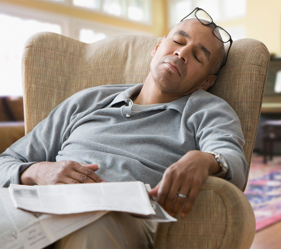 man napping in easy chair with glasses on head and newspaper in lap
