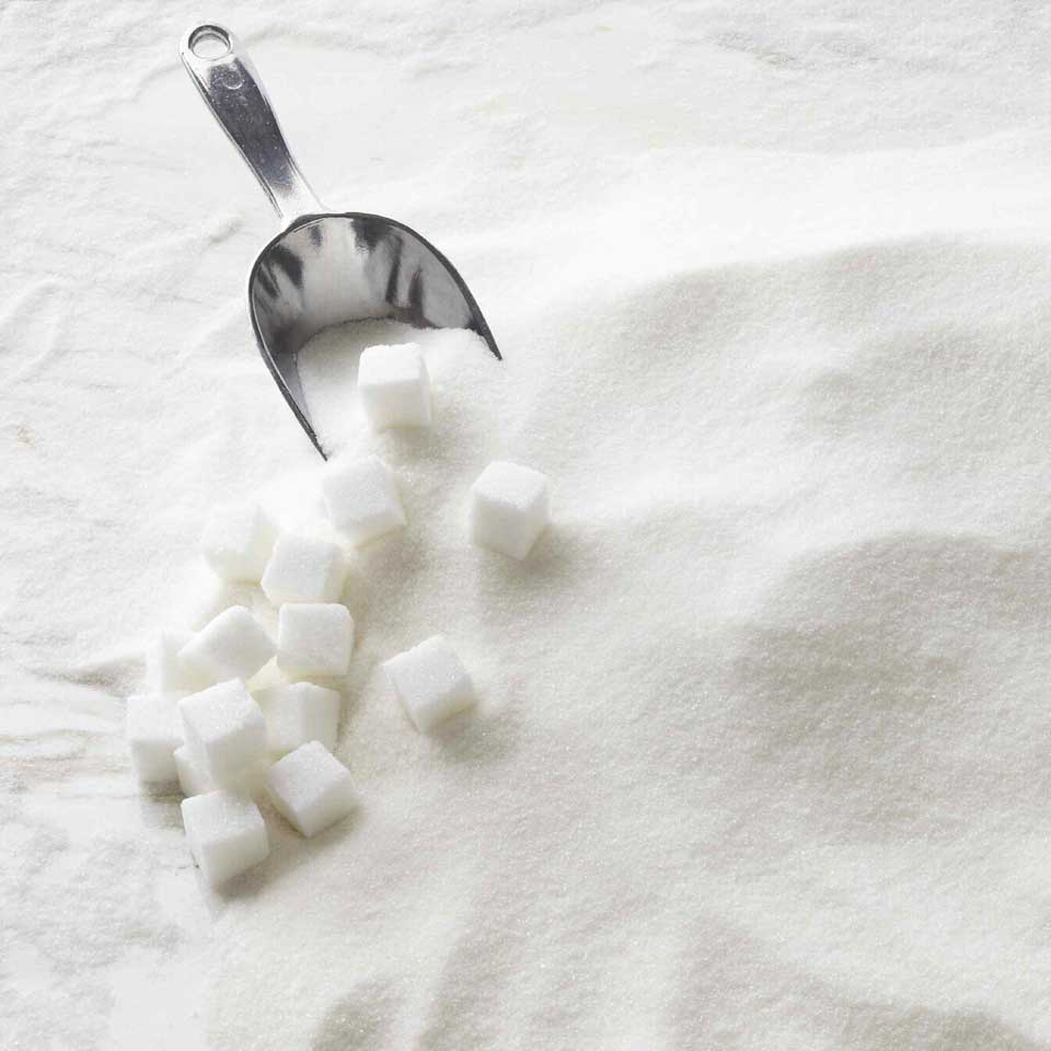a pile of granulated sugar with a scoop and sugar cubes