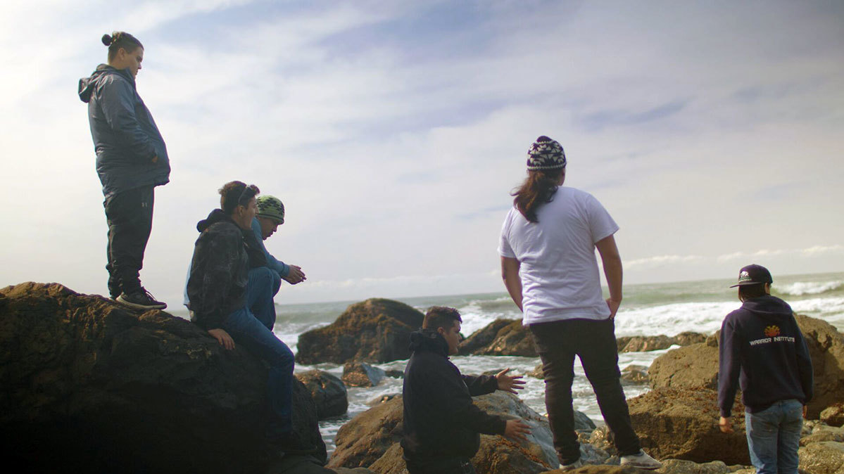 a group of young men sit on rocks by the ocean