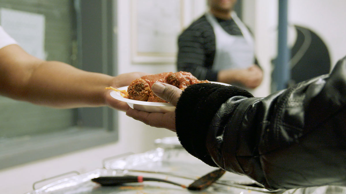 a hand holding a plate of food is reaching to give it to another hand