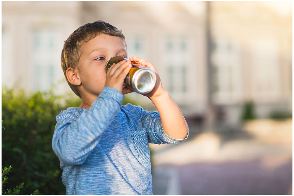 child drinking canned soda