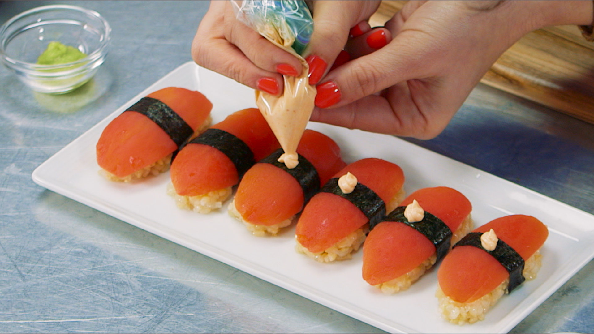 hands piping a Sriracha mayo sauce on top of sushi