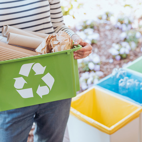 woman holding a recycling bin full of paper products