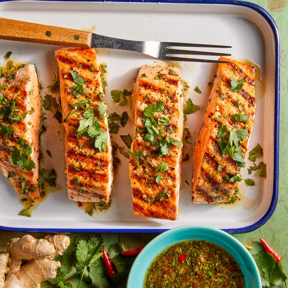 grilled salmon on a platter with fresh cilantro garnish