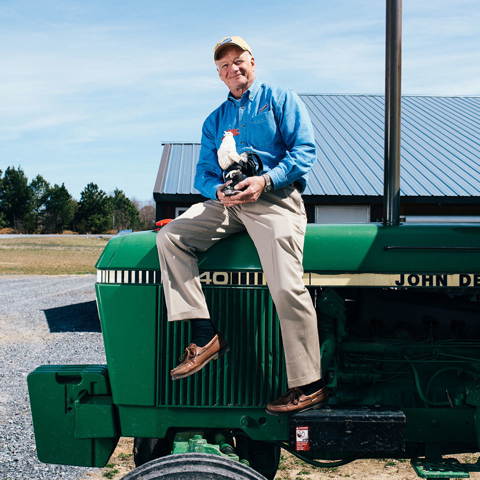 Jim Perdue sits on a green tractor holding a chicken statue