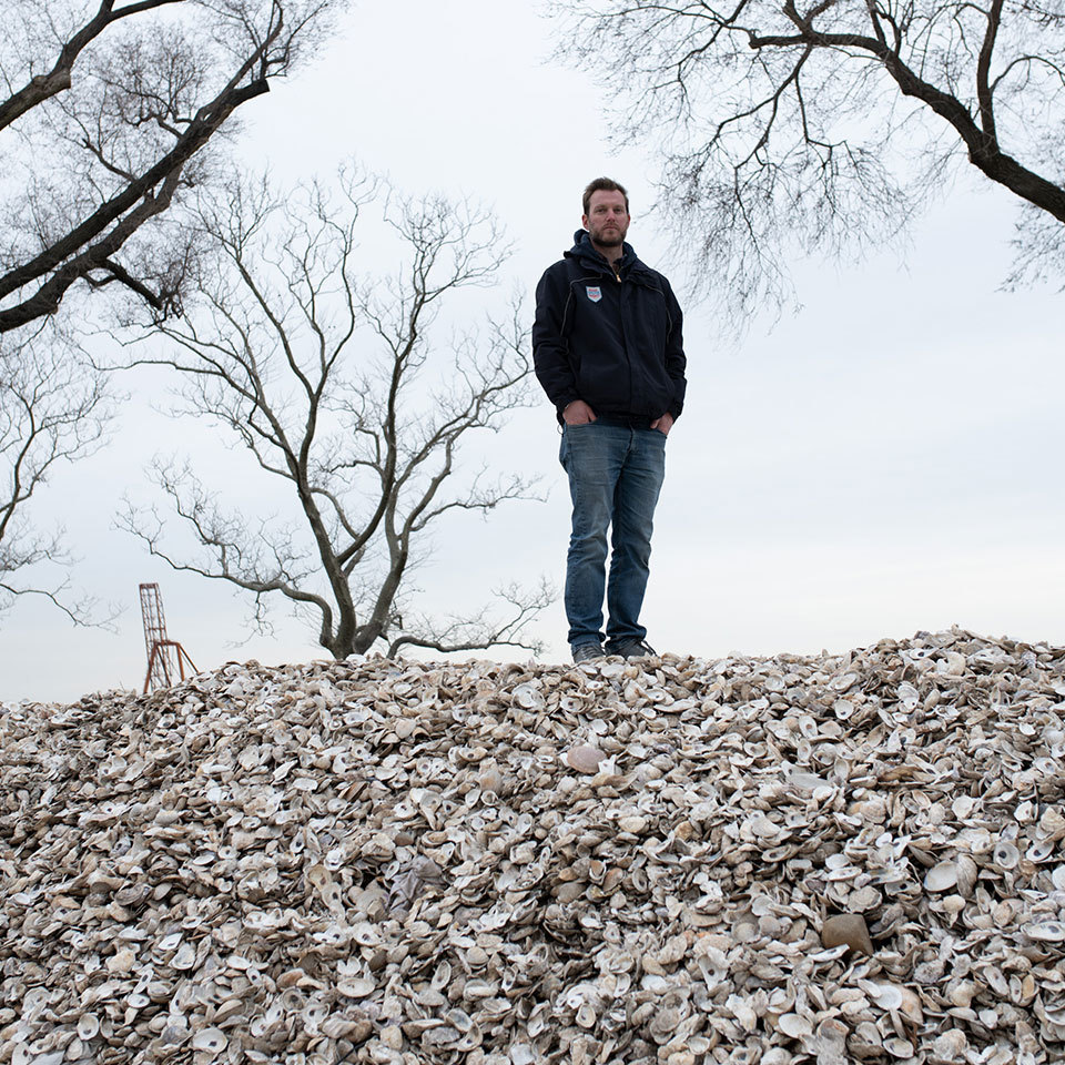 Pete Malinowski of The Billion Oyster Project stands on a hill of oyster shells