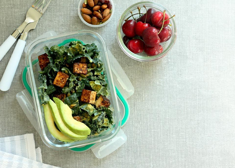 kale caesar salad with tofu croutons, bowl of cherries, and small container of almonds