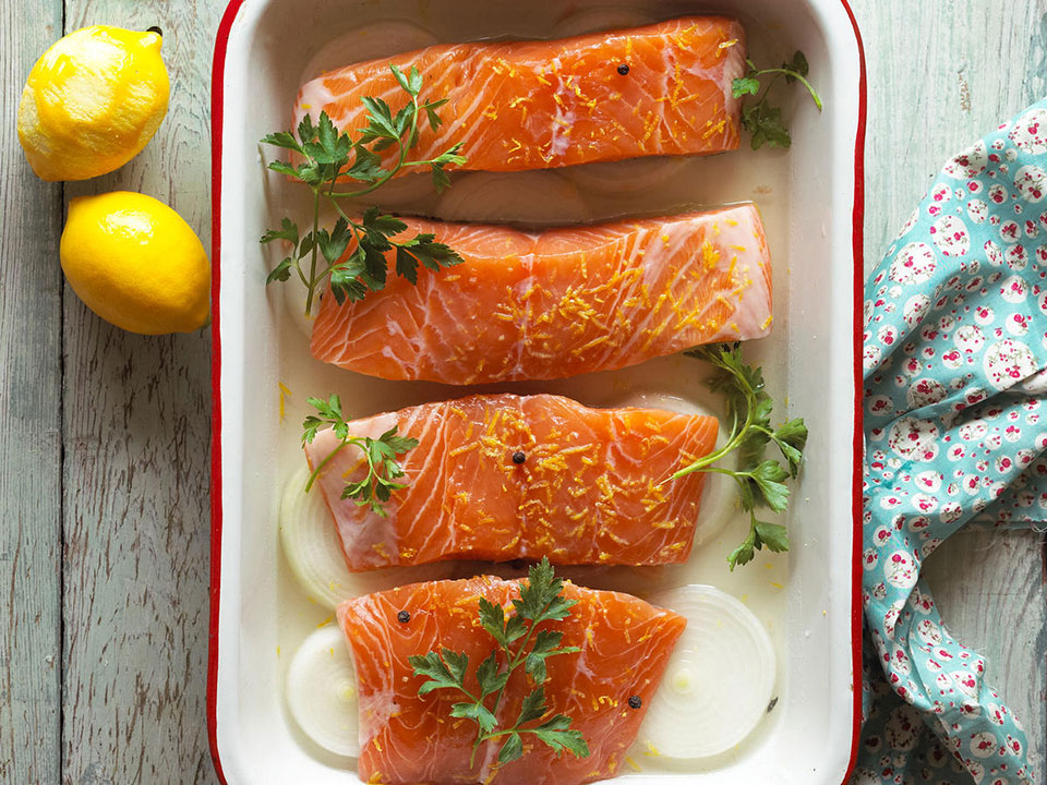 prepped raw salmon with onions, herbs and lemon