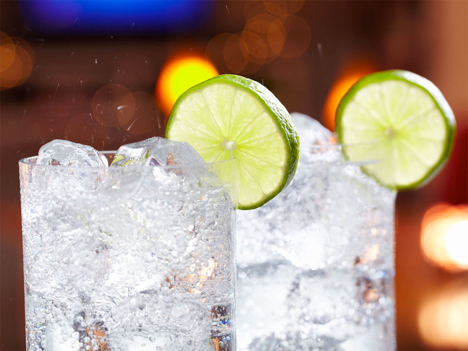 2 glasses of fizzing clear liquid garnished with a lime slice