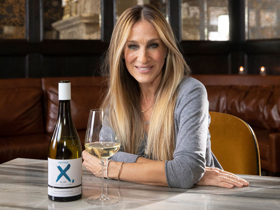 Sarah Jessica Parker smiling and sitting at a table with a bottle of wine and a filled wine glass
