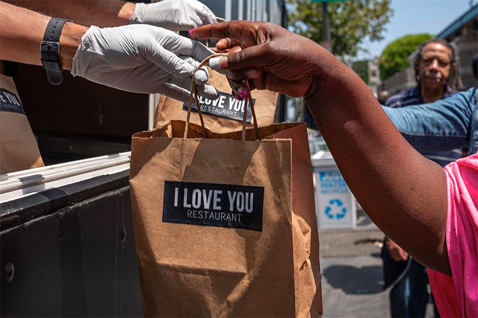 people handing over a food bag with I Love You Restaurant logo sticker to a person at the beginning of a line of people