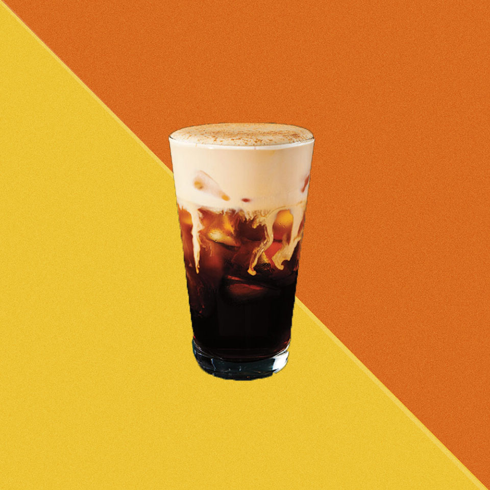 Glass of Nitro Cold Brew with pumpkin spice sprinkled on top of the delicious looking cream foam at the top