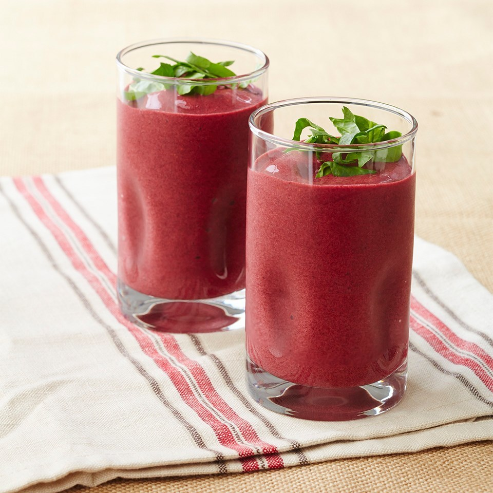 2 glasses of berry smoothies with herb garnishes