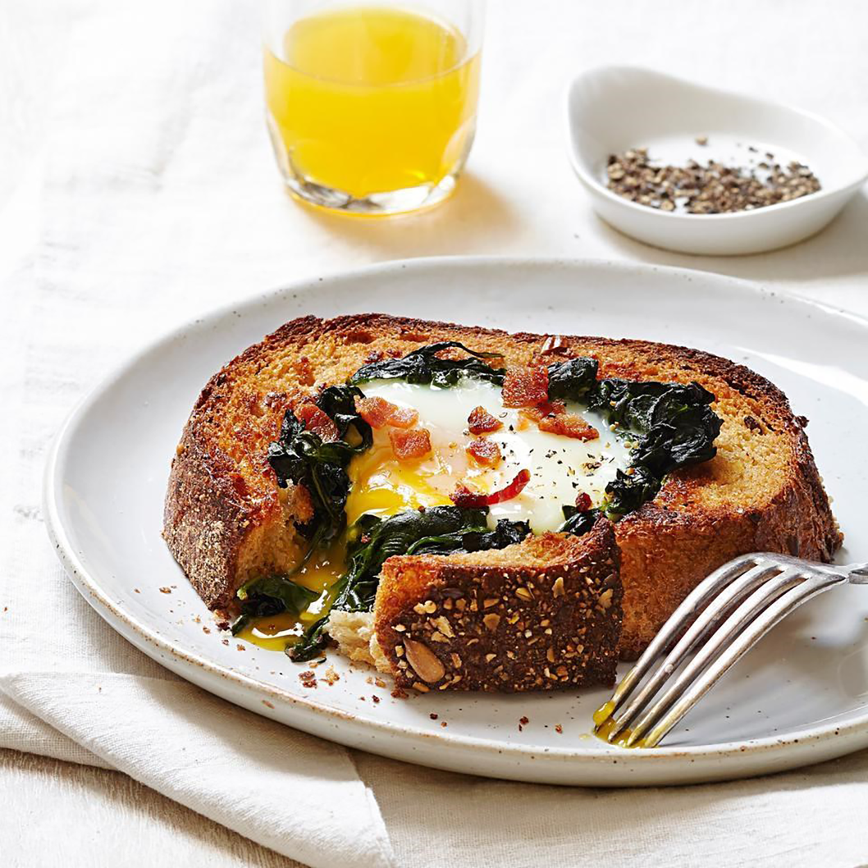 This traditional breakfast dish is elevated with festive green spinach and savory bacon for a Christmas-worthy meal.