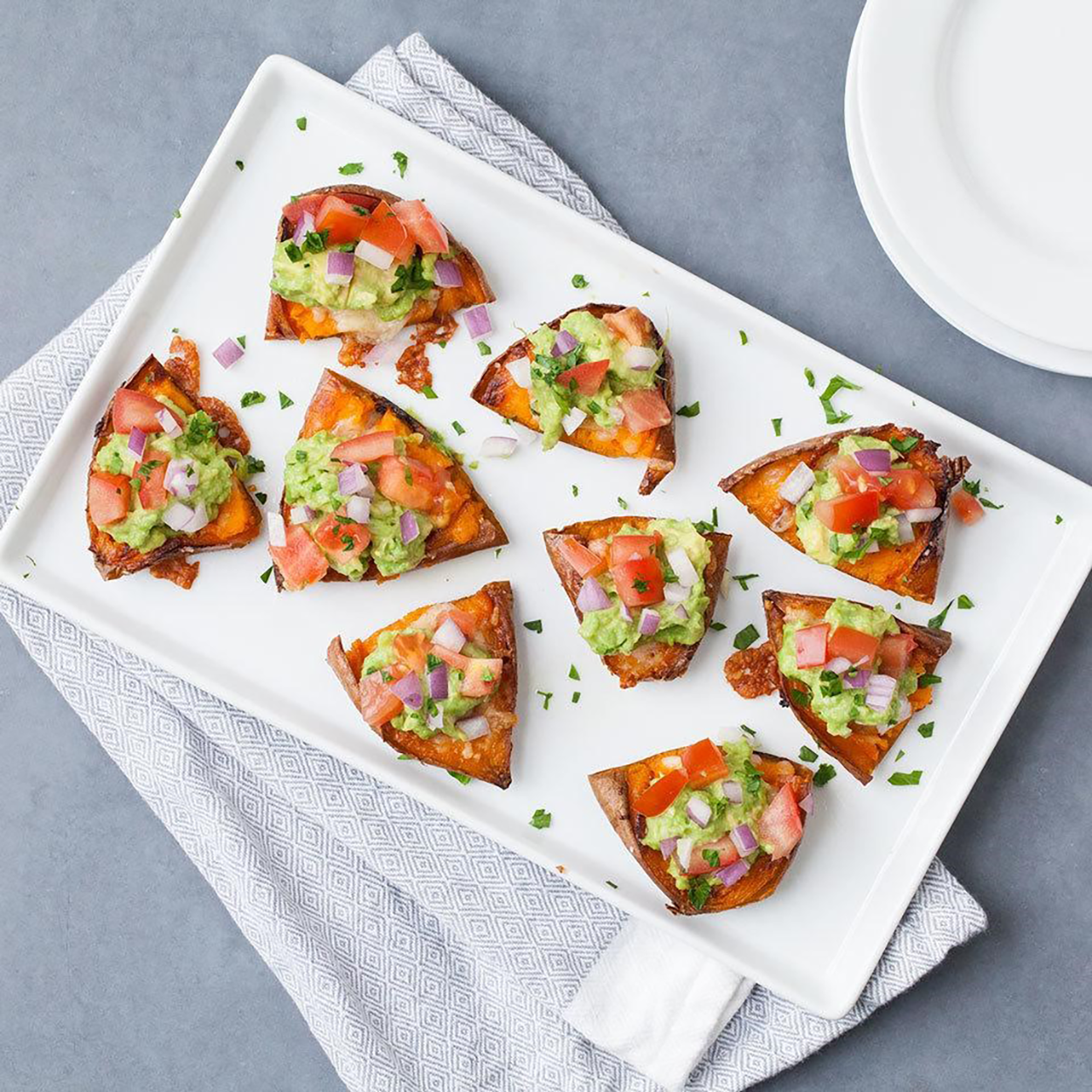 Top crispy sweet potato skins with guacamole for a healthy take on classic potato skins in this easy crowd-pleasing recipe.