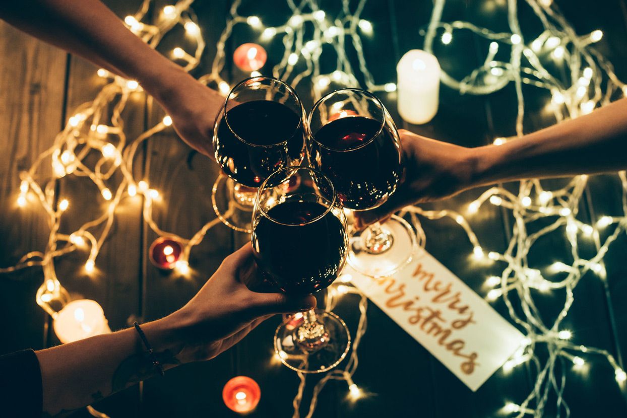 3 hands holding wine glasses together to cheers with Christmas lights and decor in the background