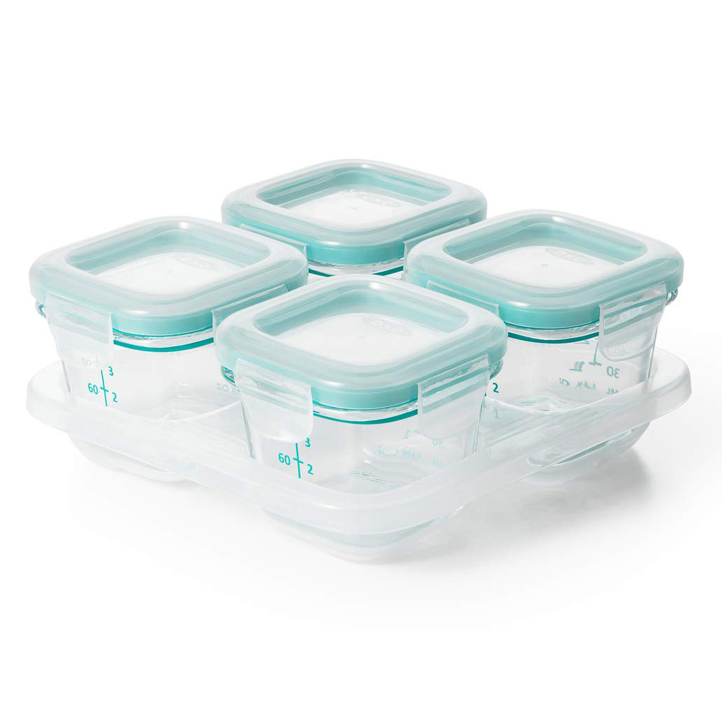 4 small glass baby food containers with measurements on the side and plastic lids