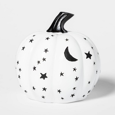 white faux pumpkin with black stars and moons painted on